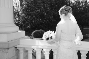 Back of brides dress as she leans on the ledge of a outdoor stairwell.