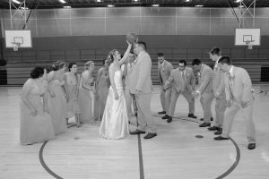 Bride and groom playing basketball with their bridal party at a school gym.