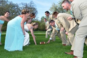 Bride and groom playing football with bridal party on the day of the wedding.