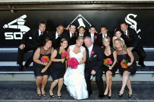 Bride and groom with bridal party in the Chicago White Sox's dugout.