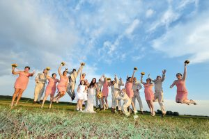 Bride and groom in an open field with their bridal party jumping for joy!