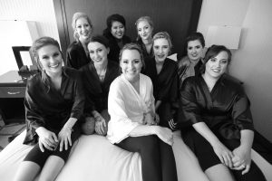 Bride with bridesmaids posing on bed with matching robes.