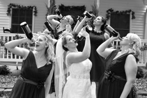 Bride and bridesmaids posing with wine bottles held up as if they are drinking them.