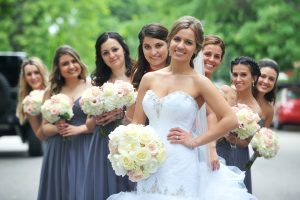 Bride with bridesmaids faces fanned out over her shoulders.