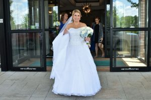 Bride walking out of hotel going to car that will take her to the ceremony.