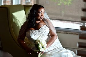 Bride sitting on the edge of a chair looking out the window with beautiful sunlight falling softly on her face.