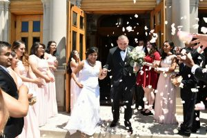 Bride and groom coming out of church to a shower of flower petals.