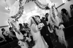 Bride and groom kissing at the end of the church aisle under canopy.