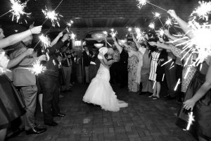 Bride and groom kissing while guests are holding sparklers.