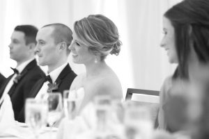 Bride and groom listening to the best mans toast and smiling.
