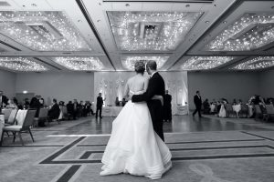 Bride and groom looking into their decorated reception hall with their backs to the camera.