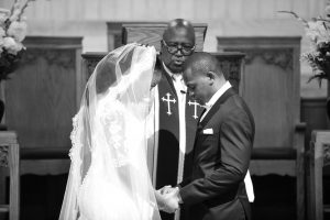 Bride and groom at the church altar praying with the minister during their wedding ceremony.