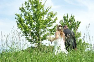 Bride and groom walking away from the camera in a field of tall green grass.
