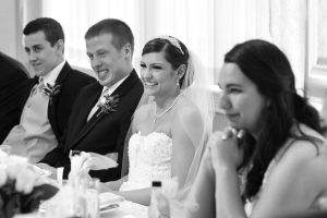 Bride and groom at the head table laughing at the dads speech.