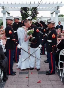 Bride and groom kissing while military members salute them with swords.