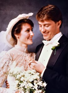 Bride and Groom from the 1980's at a portrait backdrop. Bride is looking at the groom while the groom is looking at the ring he just put on brides finger.