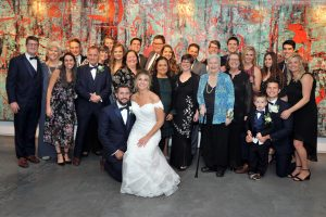 Bride and groom family photo taken with mural wall behind them at Zhou B Art Center.