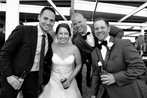 Bride and groom with two friends sharing a beer together.