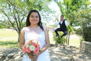 Bride in foreground with groom jumping in the background.