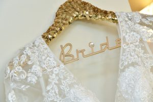 Wedding dress on gold hanger with word bride showing.