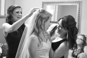 Bridesmaids putting on the brides veil.