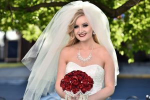 Close up of bride outside with her bright red bouquet of roses.
