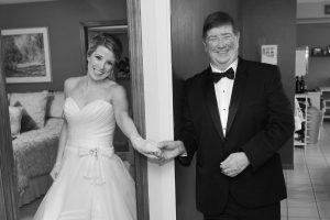 Dad holding hands with daughter between a door waiting to see her all dressed up for her wedding.