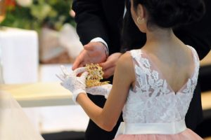 Flower girl presenting rings to the groom during the ceremony.