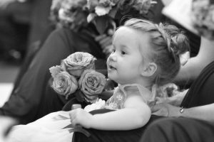 Flower girl intently watching and smiling as the ceremony takes place in the church.