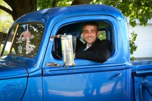 Groom driving to the church in an old bright blue ford pickup truck.
