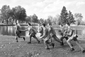 Groomsmen chasing runaway groom by lake in forest preserve.