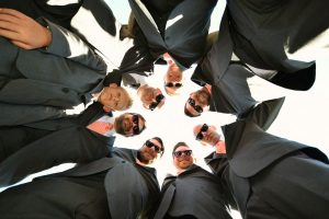 Groomsmen in a circle looking down into the camera.
