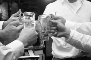 Groomsmen toasting with silver monogrammed beer steins.