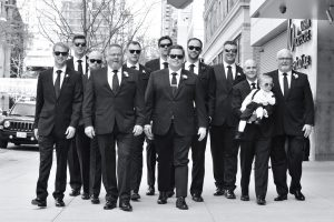 Groom and groomsmen walking on a street in downtown Chicago.