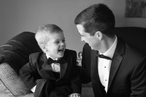 Ring bearer laughing with his dad as they wait for everyone to get ready for the wedding.