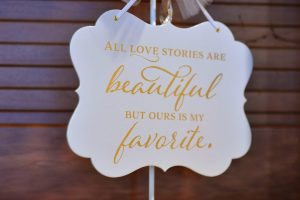 """Wedding decoration at the church that says """"all love stories are beautiful, but ours is my favorite""""."""